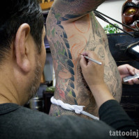 Horikazu while painting tattoo design directly on client's body.